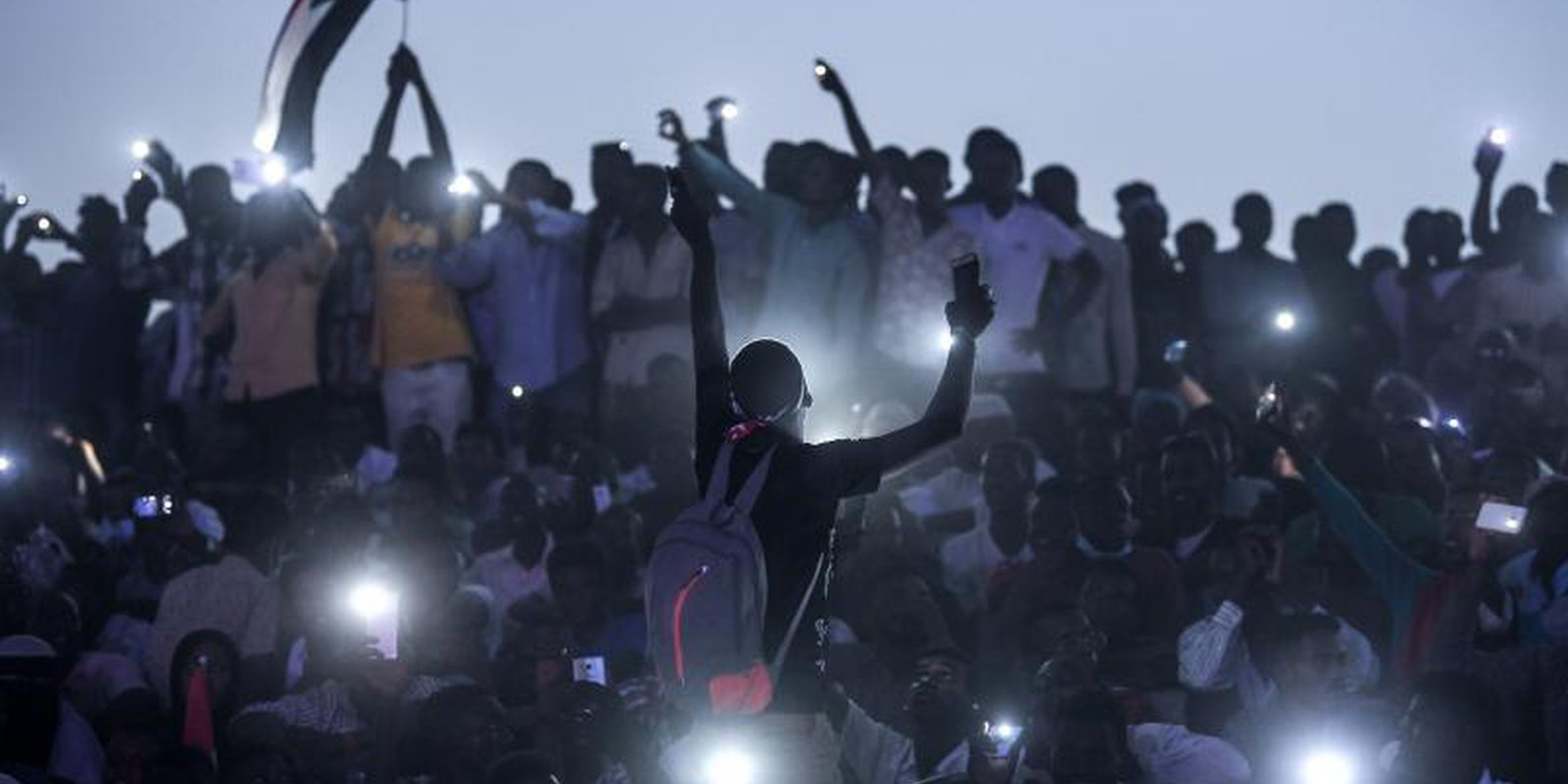 Sudanese protesters open their smartphones lights as they gather for a million-strong march outside the army headquarters in Khartoum on April 25, 2019. Photo by OZAN KOSE/AFP/Getty Images.