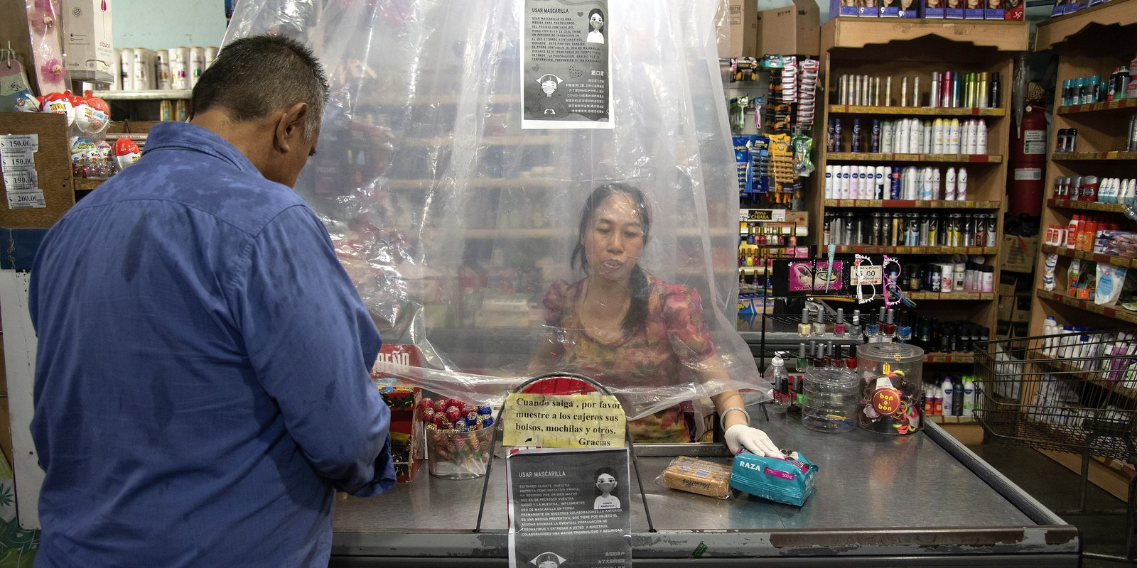 A cashier serves a costumer behind a makeshift plastic curtain due to the spread of COVID-19 in Buenos Aires, Argentina, 14 March 2020 (Photo by Lalo Yasky/Getty Images).