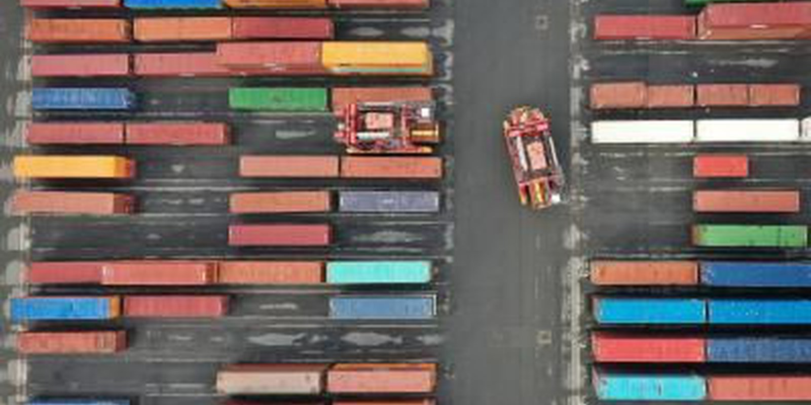 Image — An aerial photo shows Straddle Carriers moving shipping containers at Seaforth Dock in Liverpool, north west England on 17 March2021. Photo by PAUL ELLIS/AFP via Getty Images.
