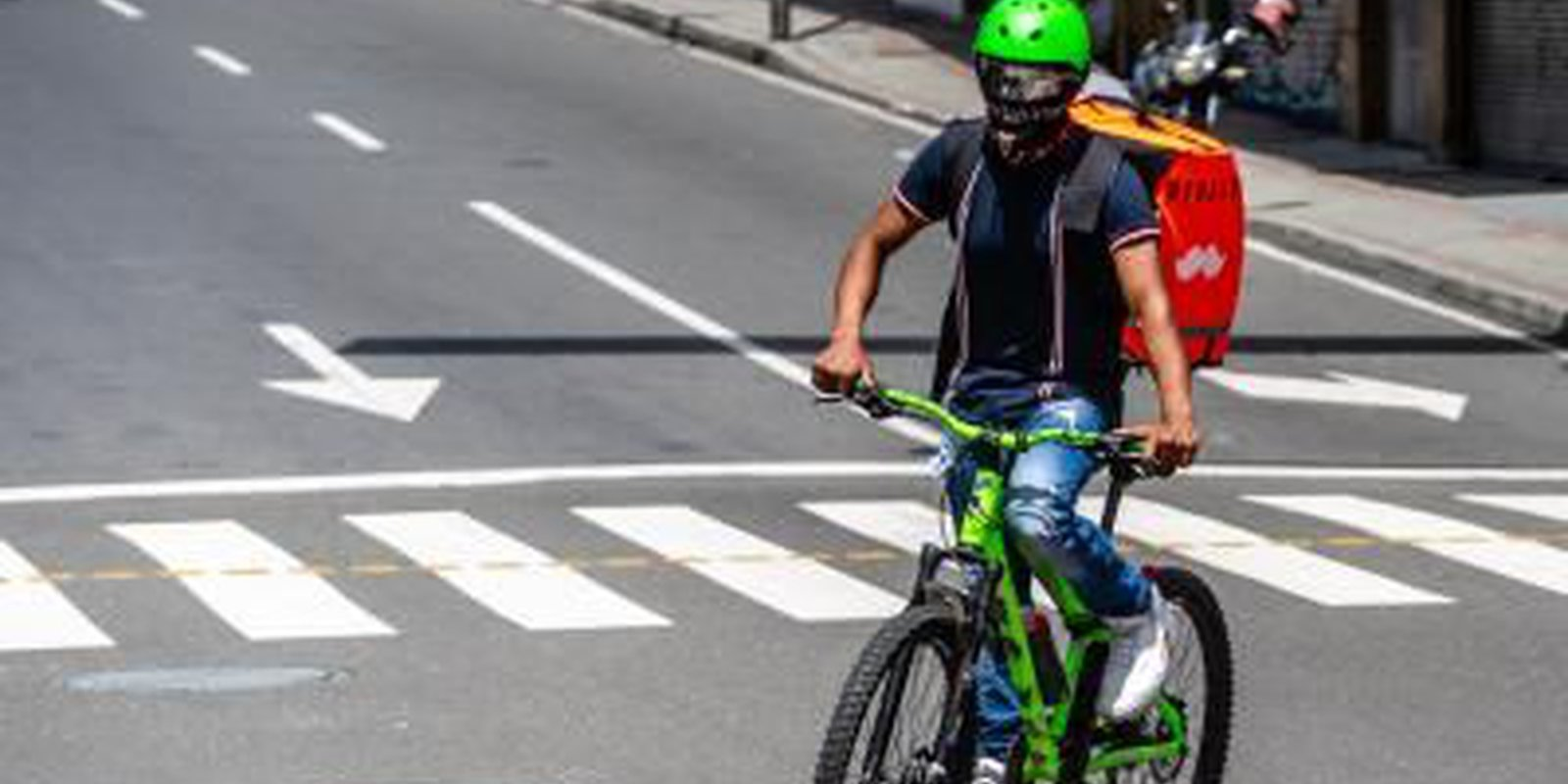 A delivery courier wearing a protective mask rides through Medellin, Colombia, on 24 July 2020.