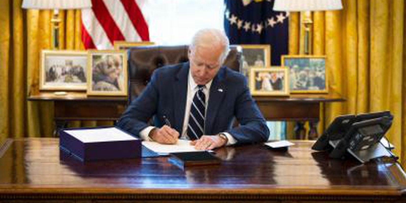 Image — US President, Joe Biden, signs theAmerican Rescue Plan into law on 11 March 2021 at the Oval Office. Photo: Getty Images.