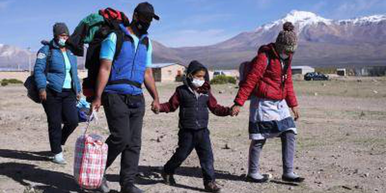 A Venezuelan migrant family is seen after crossing the border between Bolivia and Chile. Photo by Ignacio Munoz/ AFP via Getty Images.