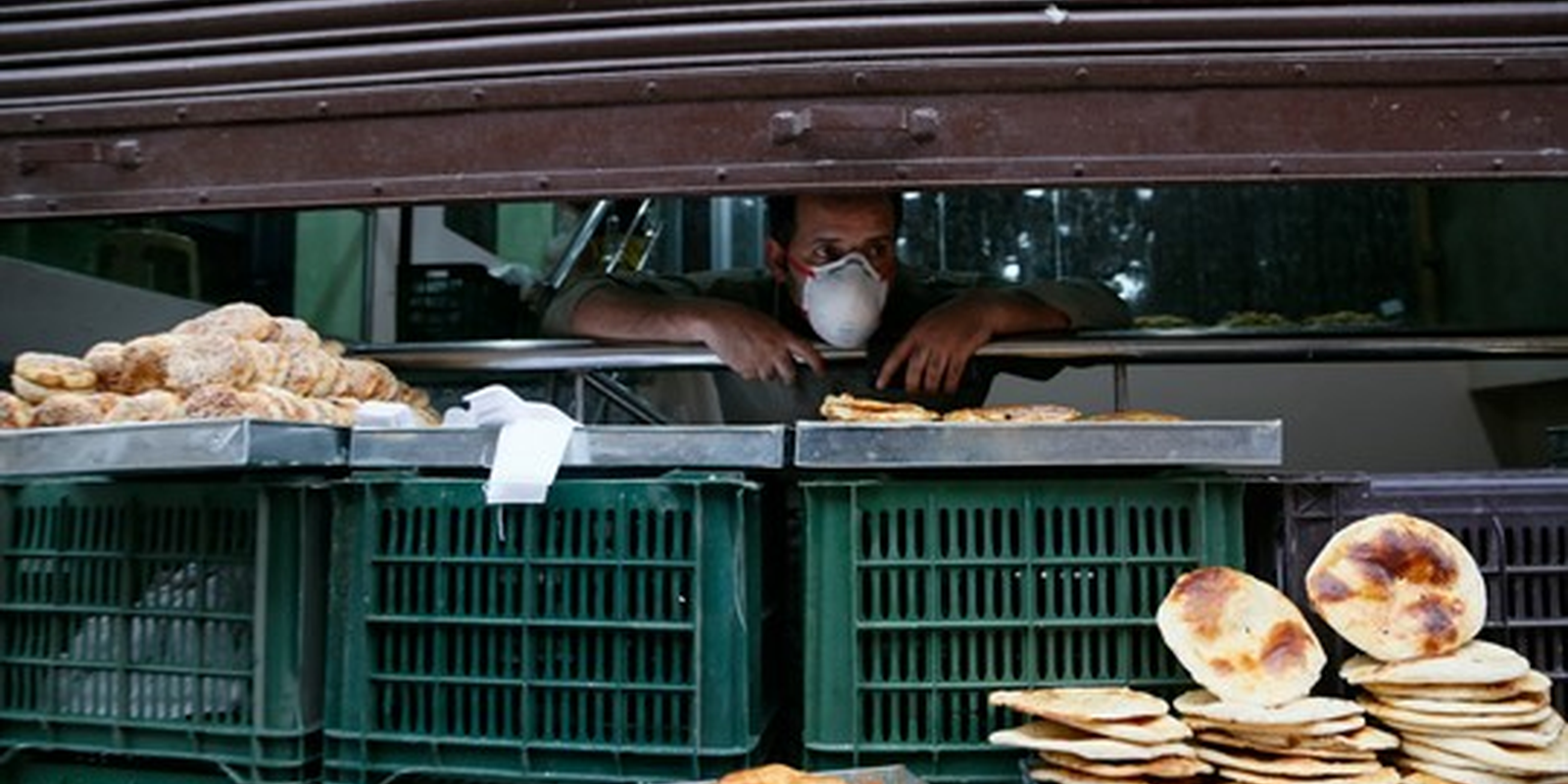 A Kashmiri man waits for customers behind a half-closed shutter during a nationwide lockdown to control the spread of the coronavirus, in Srinagar, Kashmir, May 16, 2020 (AP photo by Mukhtar Khan).