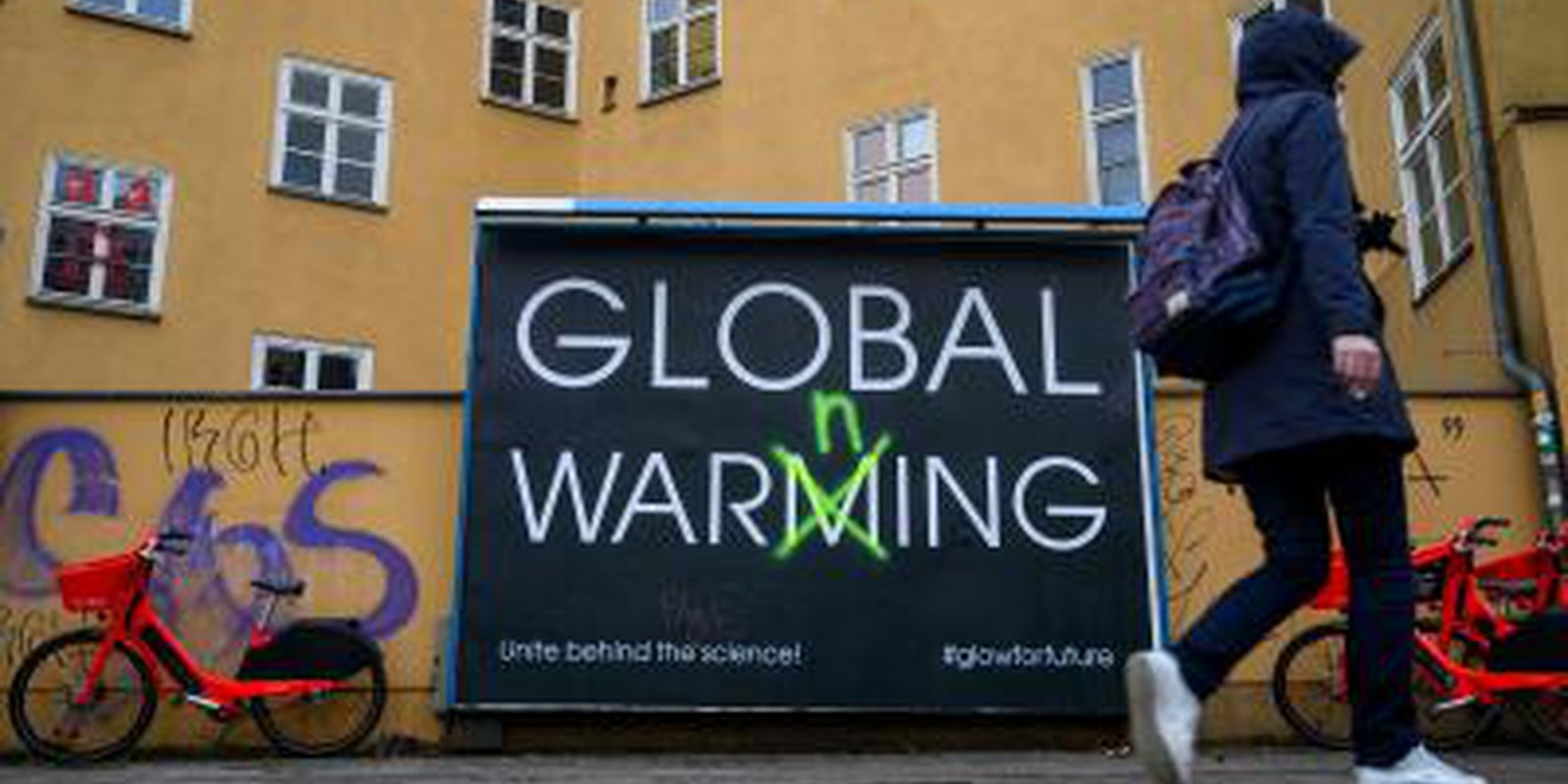 Image — Billboard in Berlin warnspeople to acknowledge all the challenges posed by global warming.Photo by JOHN MACDOUGALL/AFP via Getty Images.