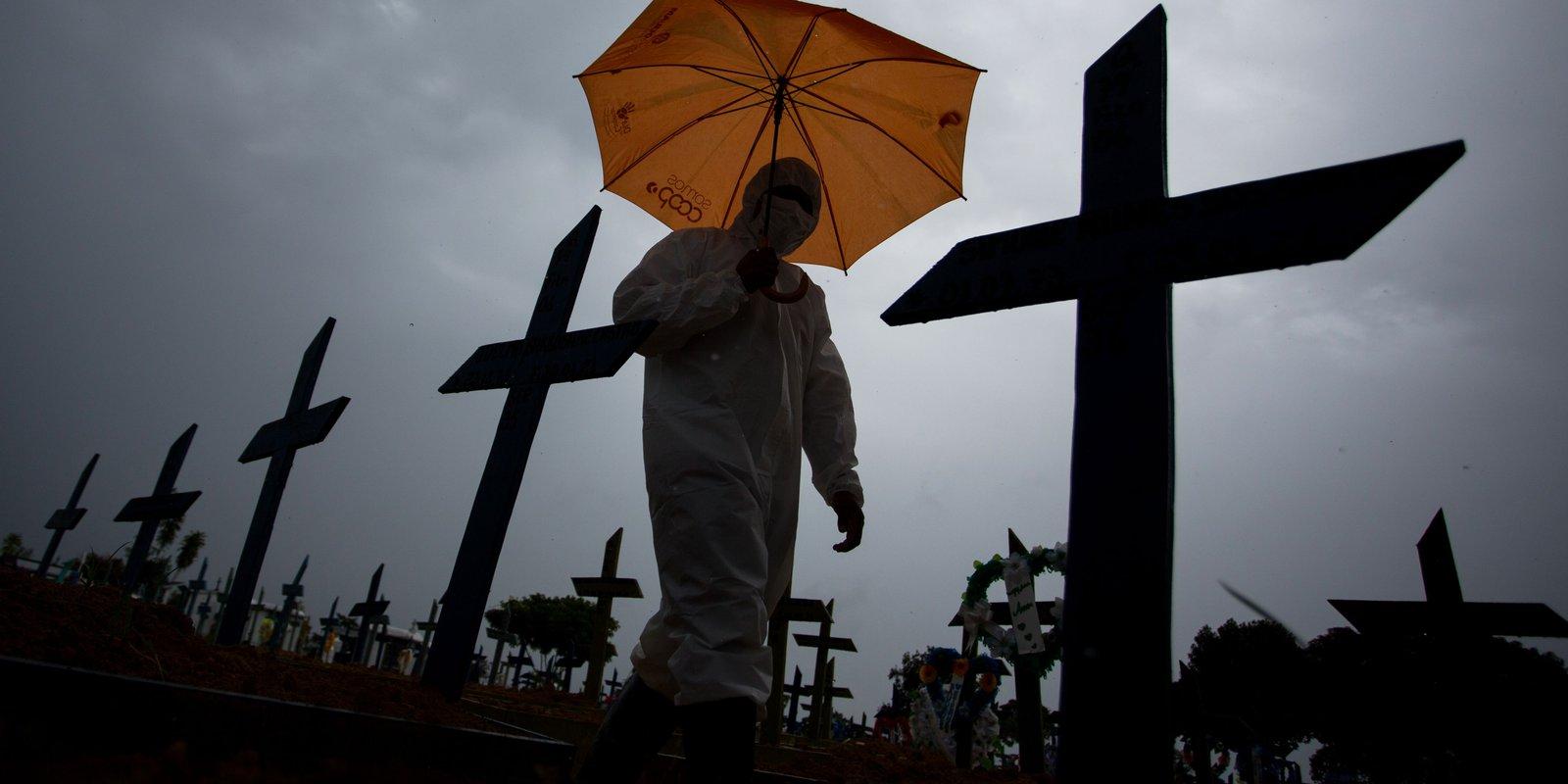 Walking past crosses marking the COVID-19 burials at the Nossa Senhora Aparecida cemetery, in Manaus, Brazil. Photo by MICHAEL DANTAS/AFP via Getty Images.