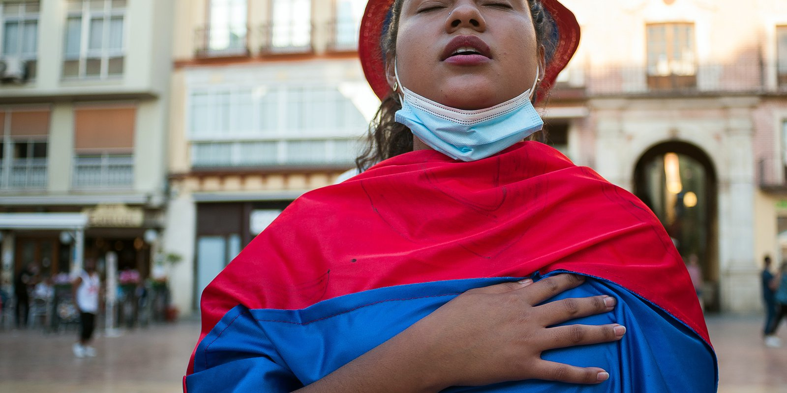 Image — Protester wrapped ina Colombian flag singsa hymn during ademonstration against the government of President Iván Duque. Photo by Jesus Merida/SOPA Images/LightRocket via Getty Images.