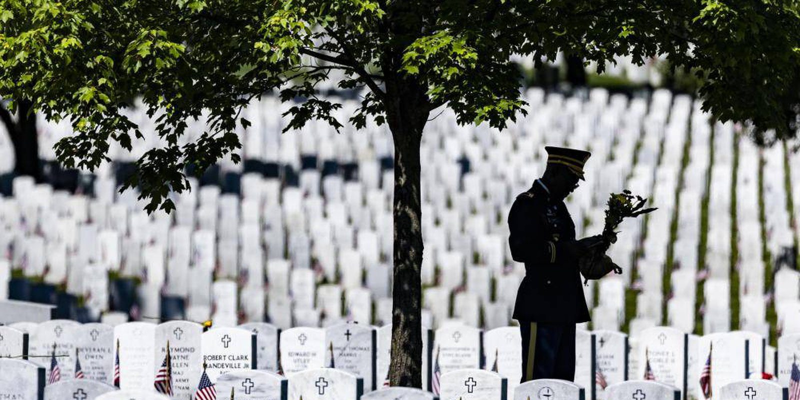 Image — A USsoldier stands with a bouquet of flowers amongheadstones of those killed during the wars in Iraq and Afghanistan in Section 60 of Arlington National Cemeteryin Arlington, Virginia. Photo by Samuel Corum/Getty Images.
