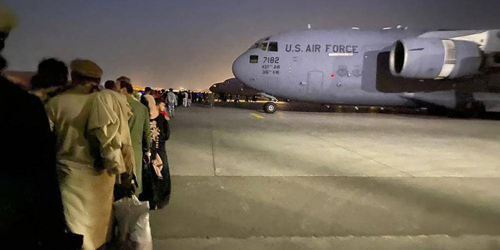 Image — Afghansqueue toboard a US military aircraftto leave Afghanistanat the military airport in Kabul after the Taliban'stakeover. Photo by SHAKIB RAHMANI/AFP via Getty Images.