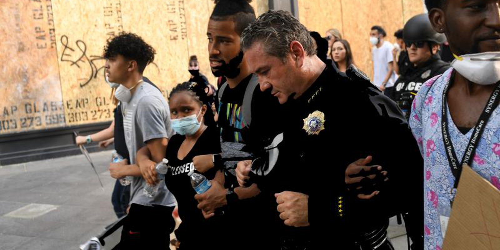 Denver police chief Paul Pazen marches arm and arm with peaceful protesters during a protest over the death of George Floyd. Photo by RJ Sangosti/MediaNews Group/The Denver Post via Getty Images.