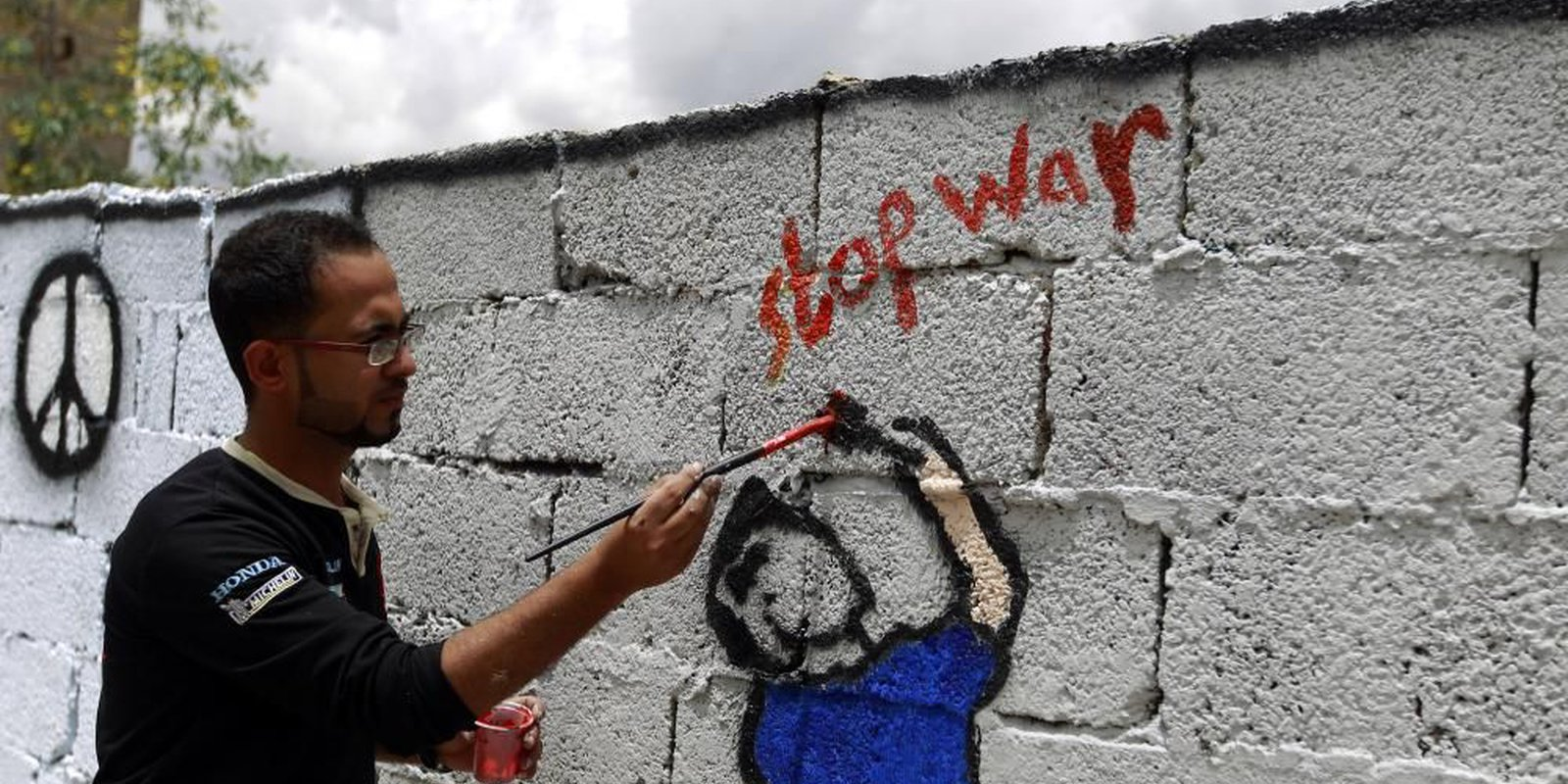 Image — A Yemeni artist painting on a wall in the capital Sanaa in support of peace. Photo byMOHAMMED HUWAIS/AFP via Getty Images.