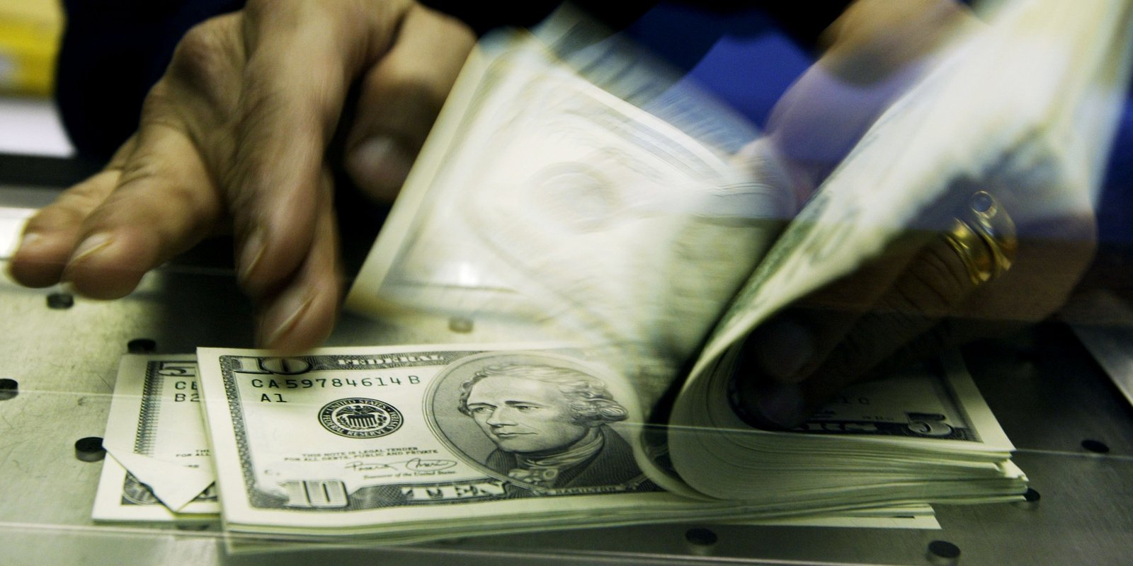 Image — CountingUSdollars at a currencyexchange. Photo by Ian Waldie/Getty Images.