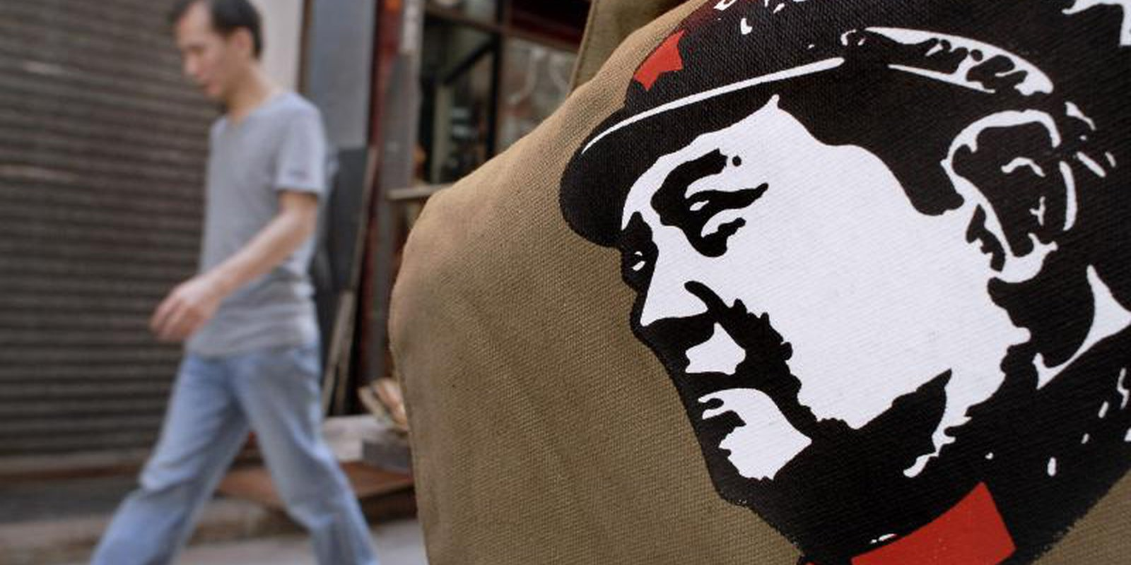 A man walks past a bag printed with the portrait of China's revolutionary leader Mao Tse-tung on display outside a shop in Hong Kong. Photo by PHILIPPE LOPEZ/AFP via Getty Images.