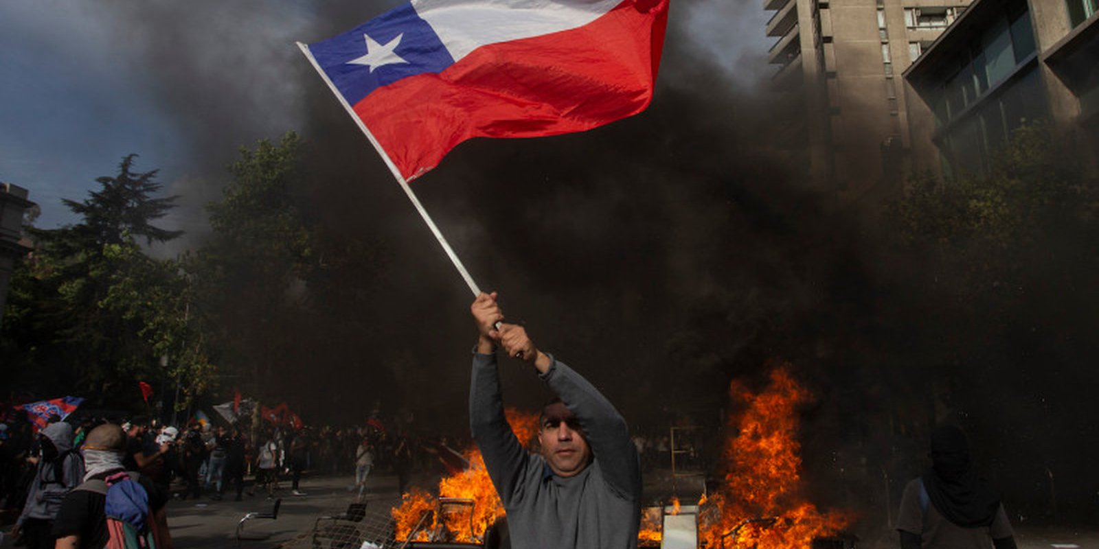A demonstrator waves a Chilean flag at a barricade during a protest against the government's economic policies in Santiago on Oct. 29. CLAUDIO REYES/AFP VIA GETTY IMAGES